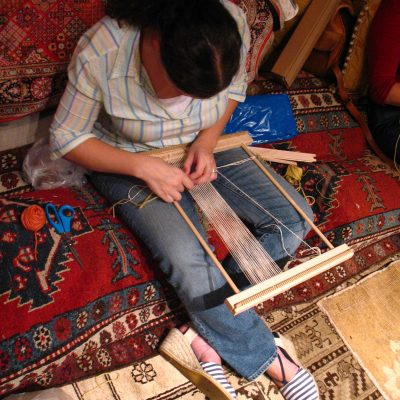 A student works on a small rug at Hayko Fine Rugs & Tapestries.